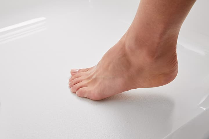 Foot stepping on textured surface of walk-in bath
