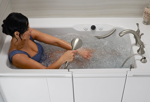 Woman using multifunction shower head in the Kohler Walk-In Bath