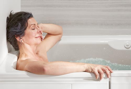 Woman relaxing in Kohler walk in tub