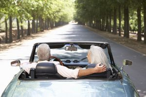 Elderly man and woman driving in car