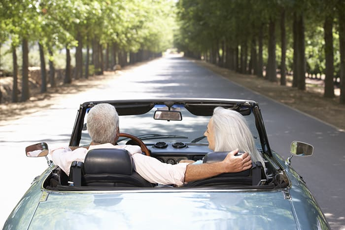 Old man and woman driving in car