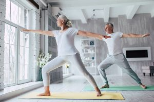 Older man and woman do yoga pose
