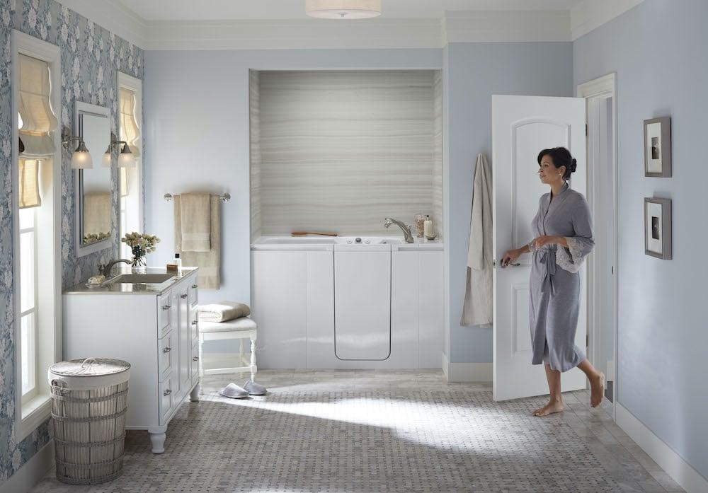 Woman enters bathroom, featuring a KOHLER Walk-In Bath.