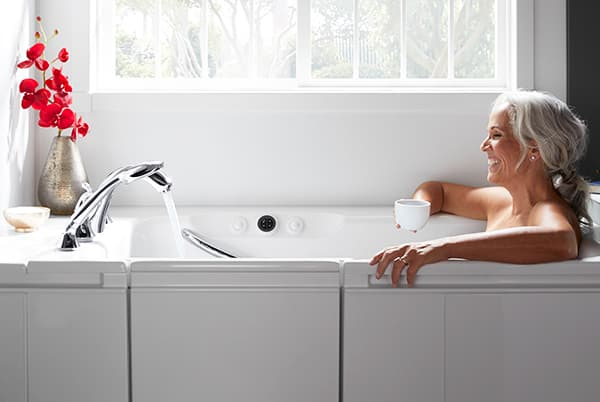 Woman holding coffee cup while bathing in walk-in bath
