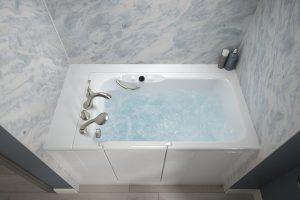 Filled walk-in bath featuring Cintilante Blue bath walls