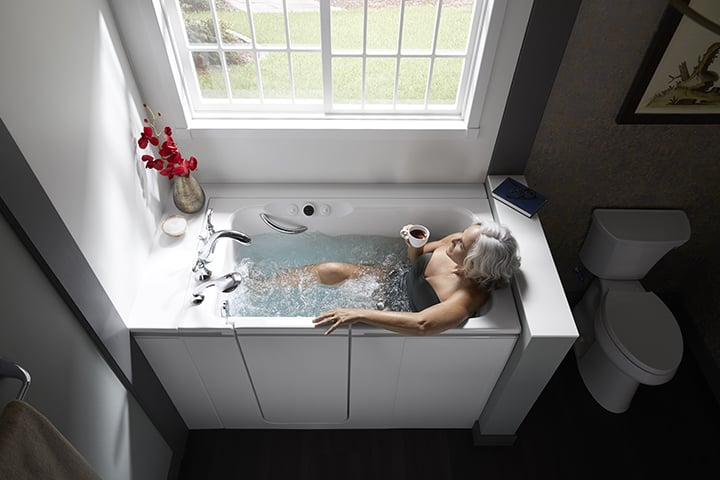 Woman drinking coffee in a walk-in bath