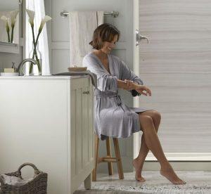 Woman applies lotion in bathroom.