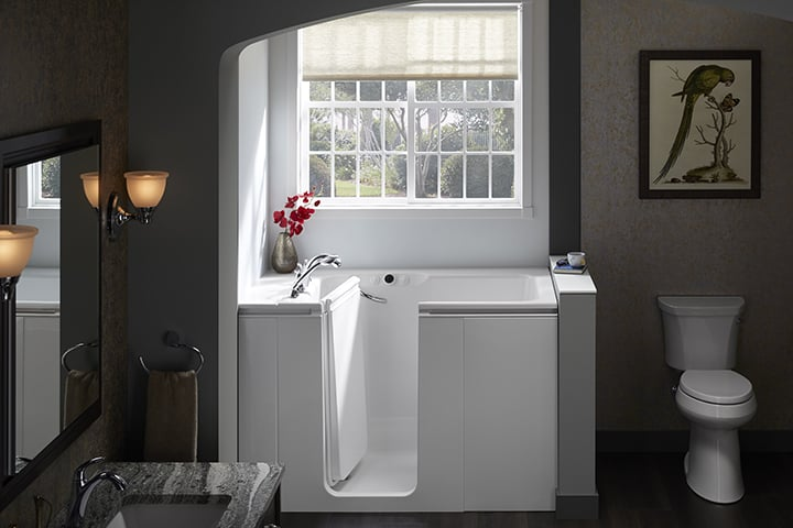 White tub against grey wall with window in background