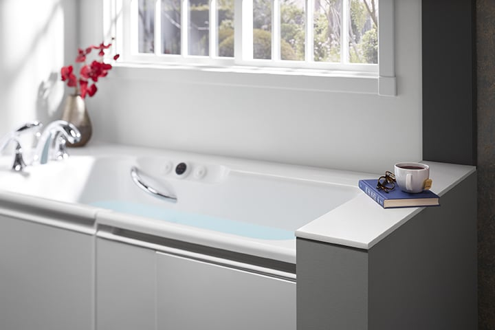 White tub against bathroom wall with book and flowers on the tub ledge