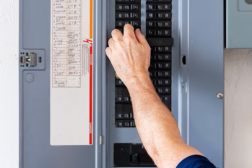 Person's hand in circuit breaker trying to fix electrical problem