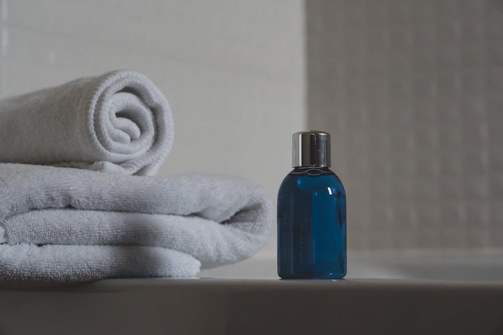 Fragrance bottle on ledge of bathtub beside stock of towels