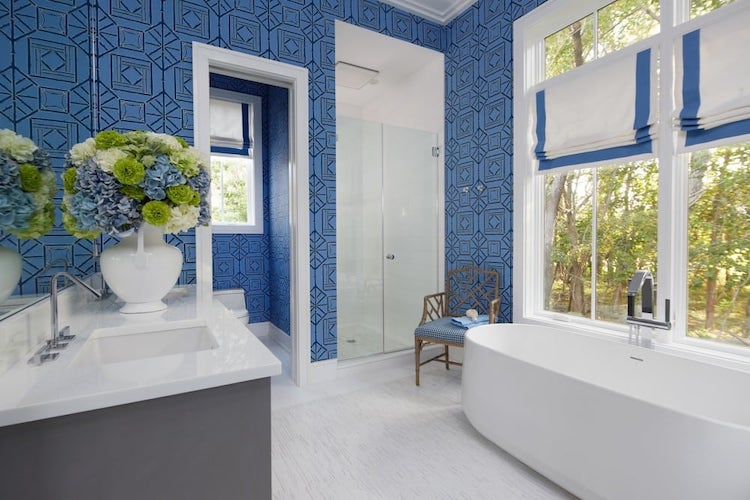 Bathroom with blue painted walls, white tub, and white sink