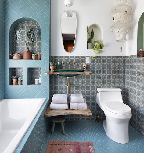 Bathroom with turquoise painted walls, white tub, and stone walls