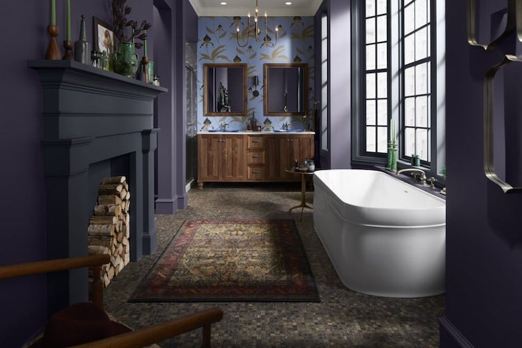 Bathroom with violet painted walls, white tub, and wooden sink