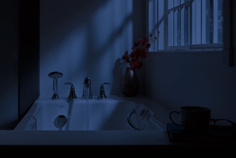 Bathtub at night with water running from faucet and moonlight shining into window