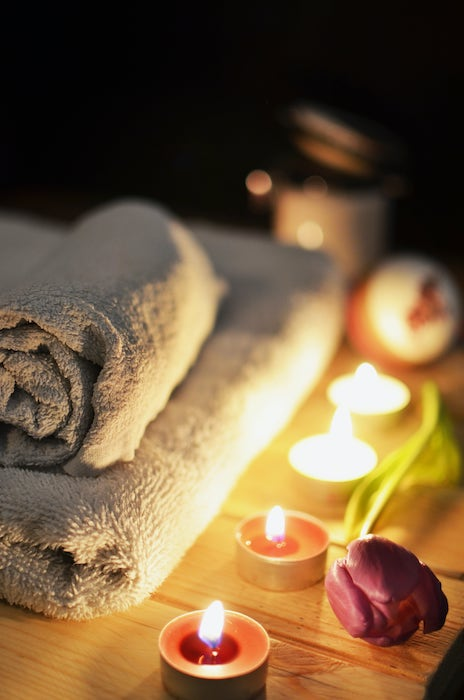 Bathroom towels on bathtub ledge with candles