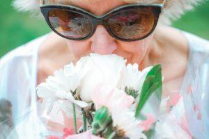 Elderly woman smelling flowers