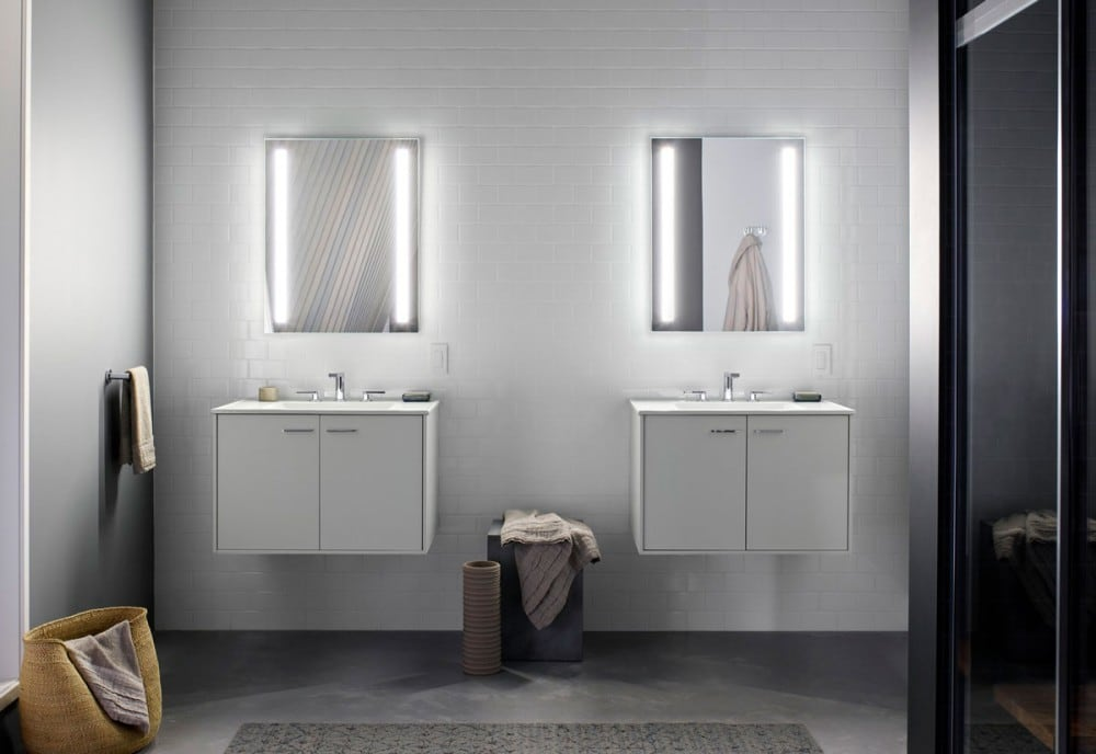 Lighted wall mirrors mounted above split bathroom vanities
