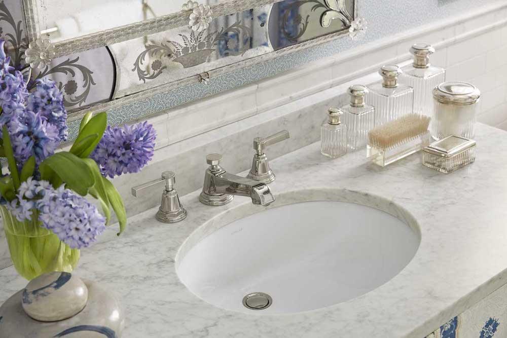 Marble bathroom countertop displaying purple flowers