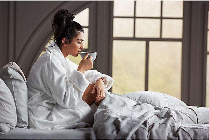 Person in bed drinking coffee in bathrobe