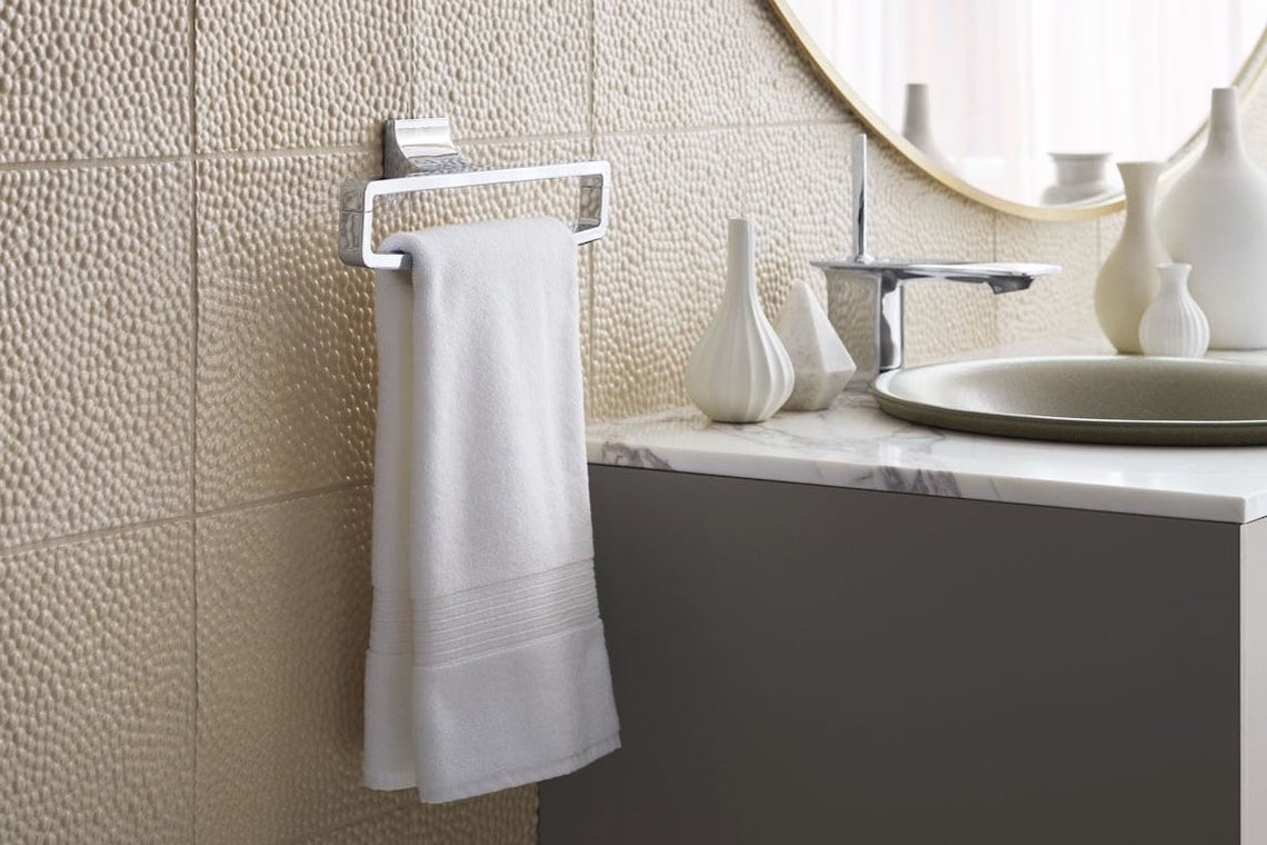 White towel on silver towel rack next to marble bathroom sink
