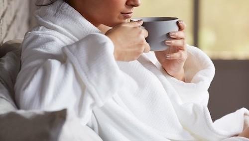 Person in bathrobe drinking warm drink