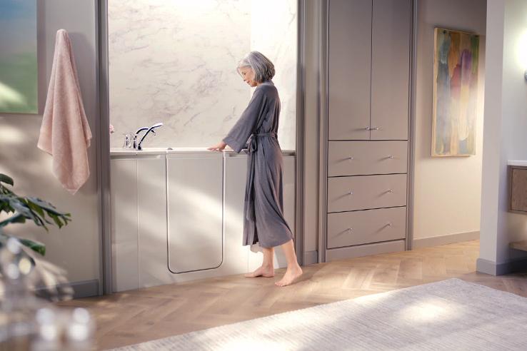 Woman standing outside Walk-In Bath on wood flooring