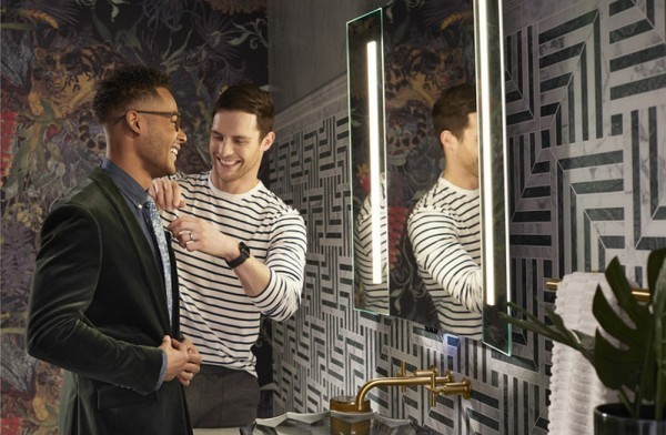 two men in front of lighted mirror